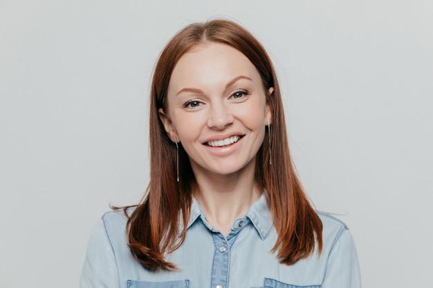 Attraente giovane donna con i capelli lisci scuri, sorrisi felicemente, vestita in camicia di jeans