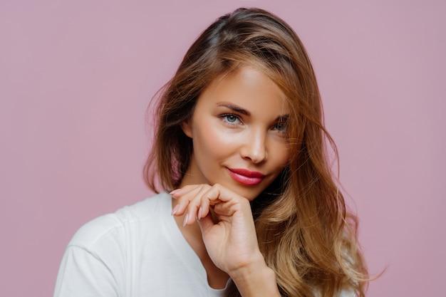 Attraente giovane donna con i capelli lunghi, manicure e trucco