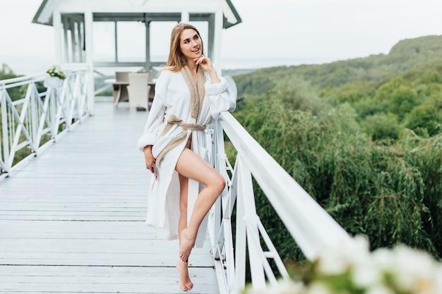 Attraente, giovane donna con il telefono sulle mani che soggiornano in terrazza estiva in montagna. tempo di bellezza. concetto di mattina.