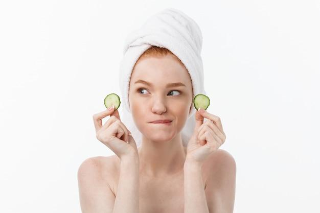 Attraente giovane donna con una bella pelle pulita. maschera bianca e cetrioli. trattamenti di bellezza e terapia termale cosmetologica.