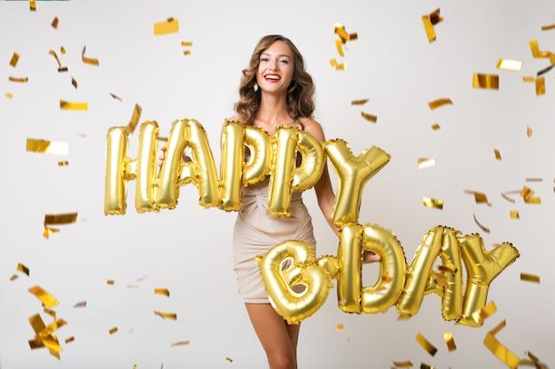 Attraente giovane donna elegante che celebra, che tiene le lettere di buon compleanno degli aerostati di aria, coriandoli dorati che volano, sorridendo felice, isolato, vestito da festa da portare