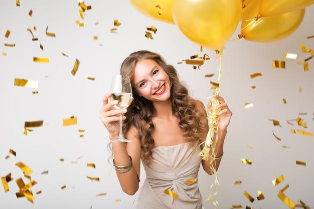 Attraente giovane donna elegante che celebra il nuovo anno, bevendo champagne con palloncini d'aria, coriandoli dorati che volano, sorridendo felice, bianco, isolato, indossando l'abito da festa