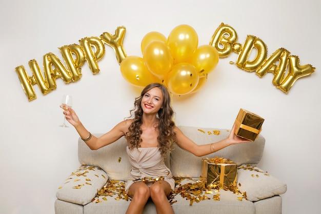 Attraente giovane donna elegante festeggia il compleanno, seduto sul divano con regali, coriandoli dorati e palloncini d'aria, umore di festa, sorridendo felice, indossando abiti da festa, bevendo champagne