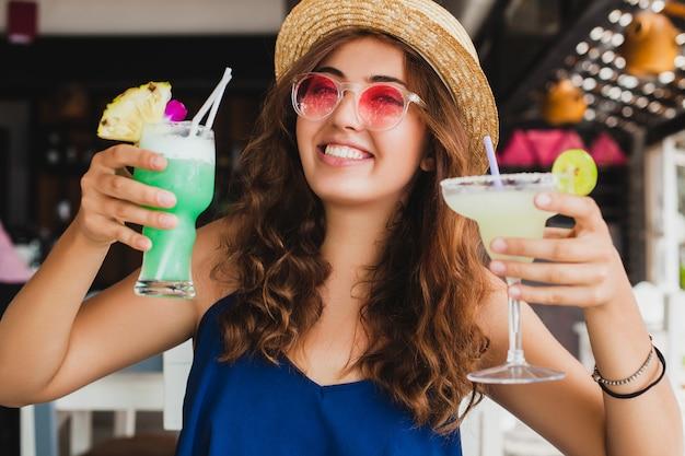 Attraente giovane donna in abito blu e cappello di paglia che indossa occhiali da sole rosa, bere cocktail alcolici in vacanza tropicale e seduto al tavolo al bar