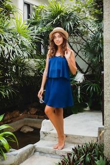 Attraente giovane donna in abito blu e cappello di paglia indossando occhiali da sole rosa camminando in hotel villa spa tropicale in vacanza in abito stile estivo, sexy