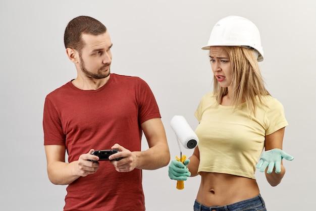 Attraente giovane donna in jeans, camicia gialla e un cappello duro solleva le mani con un'espressione scontenta perché il suo partner maschio sta riparando e dipingendo giocando ai videogiochi con un joystick