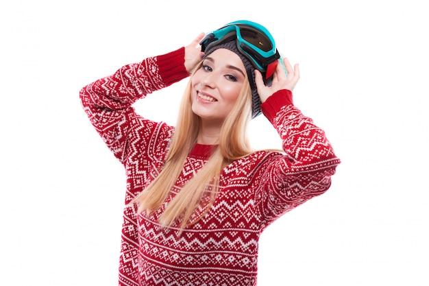 Attraente giovane donna in maglione rosso e occhiali da sci blu