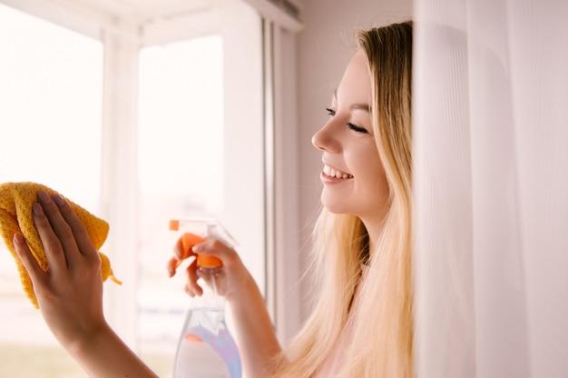 Attraente giovane donna lava la finestra della casa, servizi di pulizia