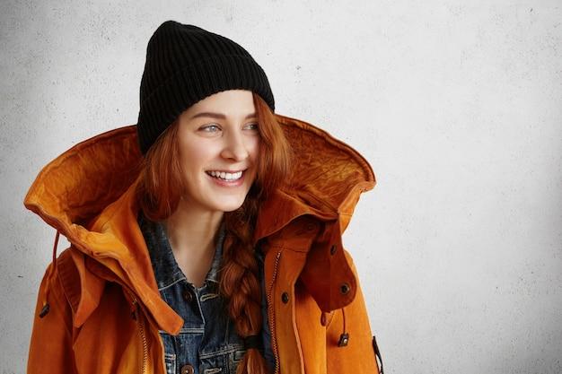 Attraente giovane donna rossa che guarda lontano con un sorriso felice pur avendo riposo al chiuso
