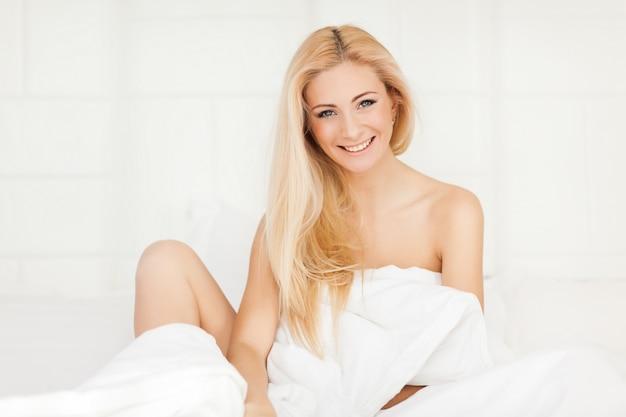 Attraente giovane donna sdraiata a letto.