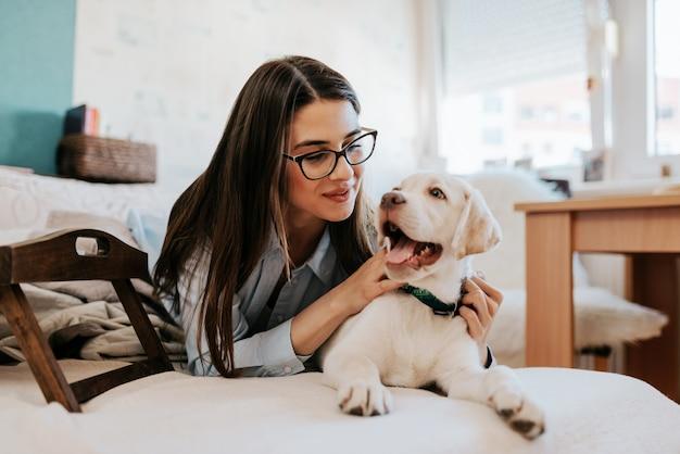 Attraente giovane donna sdraiata sul divano con il suo animale domestico e di riposo.