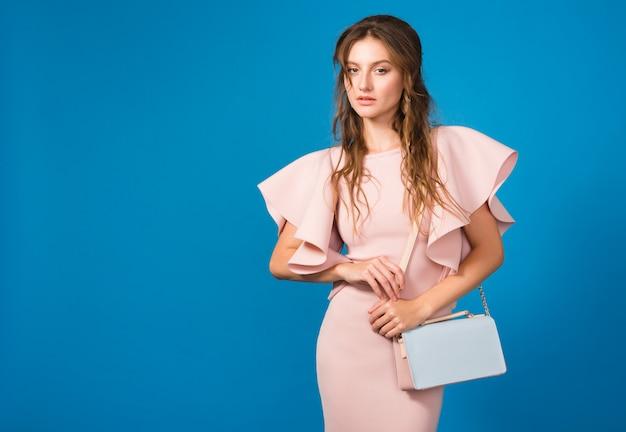 Attraente giovane donna sexy elegante in abito di lusso rosa, tendenza moda estiva, stile chic, borsa alla moda che tiene