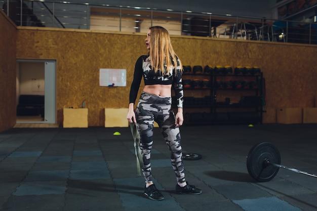 Attraente giovane donna sportiva con bilanciere. stacco.