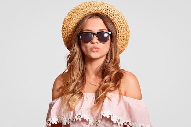 Attraente giovane femmina europea ha vacanze estive, andare in spiaggia, vestita in camicia alla moda, mostra le spalle nude