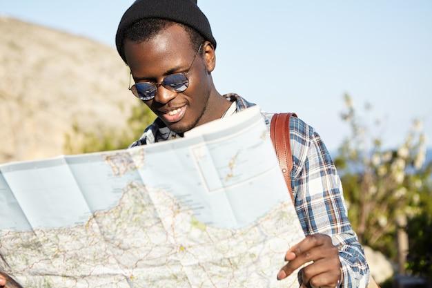 Attraente giovane hipster afroamericano sorridente in elegante cappello nero e occhiali da sole consultando la grande mappa cartacea mentre si visita la città straniera, cercando la giusta direzione, godendo le vacanze estive