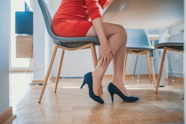 Attraente giovane impiegato femminile sentirsi piedi dolorosi togliersi le scarpe tacco alto