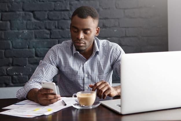 Attraente giovane imprenditore dalla carnagione scura che ha un messaggio di sms di sguardo serio sul telefono cellulare