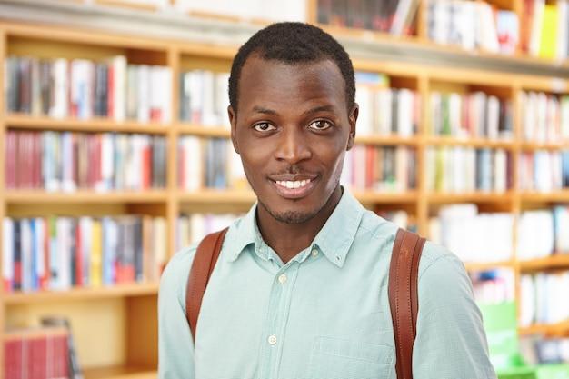Attraente giovane maschio in piedi contro gli scaffali