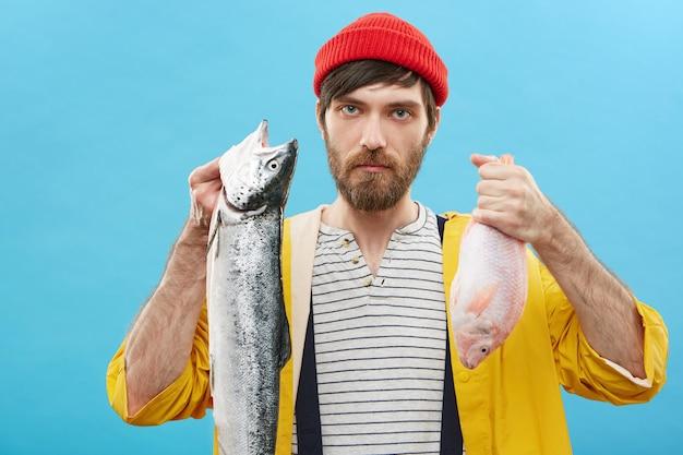 Attraente giovane pescivendolo maschio con la barba lunga che tiene due pesci nelle sue mani dopo la pesca d'altura, offrendoti di acquistare prodotti freschi. commercio e commercializzazione del pesce. hobby, sport e concetto di ricreazione