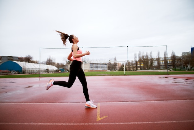 Attraente giovane ragazza fitness focalizzata arrivando al traguardo dopo lo sprint vicino al campo di calcio.