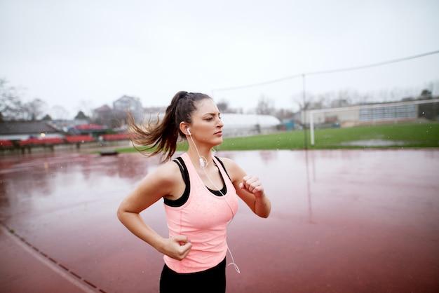 Attraente giovane ragazza fitness motivata che si precipita decisamente verso la fine della sua corsa vicino al campo di calcio mentre piove.