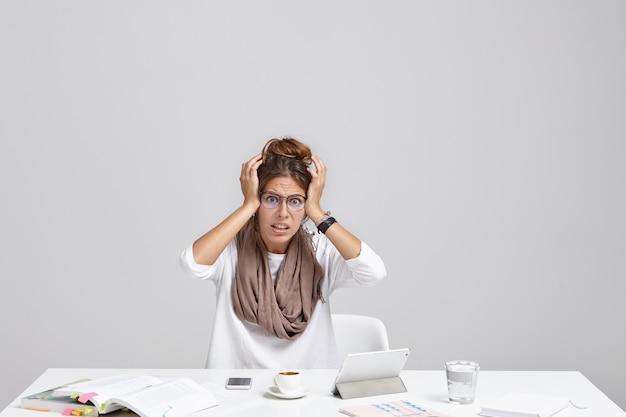 Attraente giovane segretaria femminile vestita con indifferenza in occhiali alla moda che tengono le mani sulla testa
