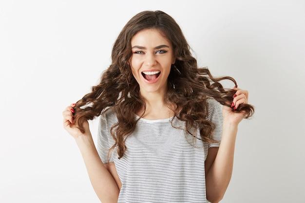 Attraente giovane signora che tiene i suoi lunghi capelli ricci castani che ride con l'espressione positiva del viso, donna emotiva, emozione isolata e felice