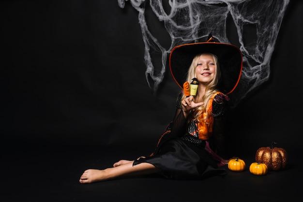Attraente giovane strega con giocattoli e zucche
