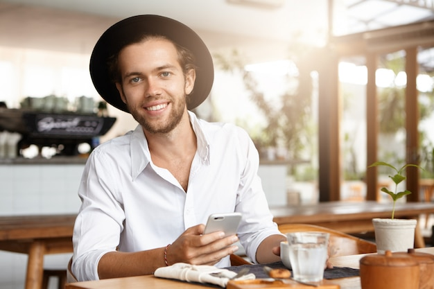 Attraente giovane uomo barbuto felice in cappello alla moda messaggi di testo tramite social network e navigazione in internet, utilizzando il wifi gratuito sul suo dispositivo elettronico durante la pausa caffè al ristorante