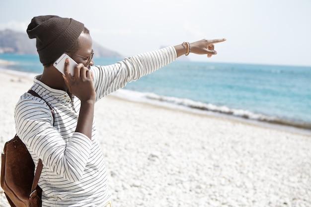Attraente giovane viaggiatore afroamericano in abiti alla moda che punta a qualcosa in mare mentre parla sul suo cellulare contemporaneo, viaggiando da solo in una città straniera. persone e vacanze estive
