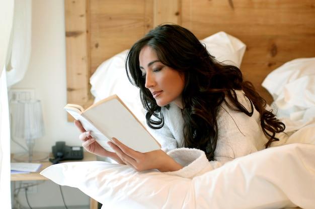 Attraente libro di lettura signora sdraiato sul letto
