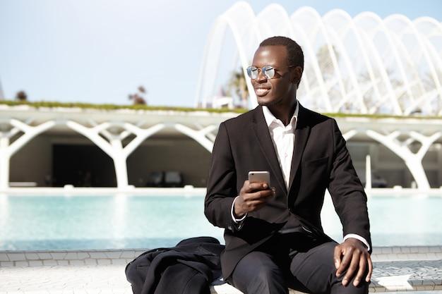 Attraente manager afroamericano in elegante abbigliamento formale e sfumature utilizzando il telefono cellulare, seduto su una panchina in ambiente urbano in attesa di colleghi per il pranzo, sorridendo felicemente mentre li nota