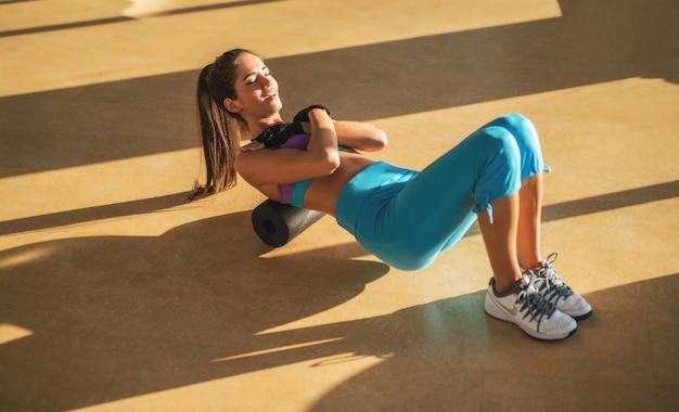 Attraente motivata concentrata giovane ragazza sottile fitness facendo esercizi sdraiati sul rullo di schiuma nella soleggiata palestra.