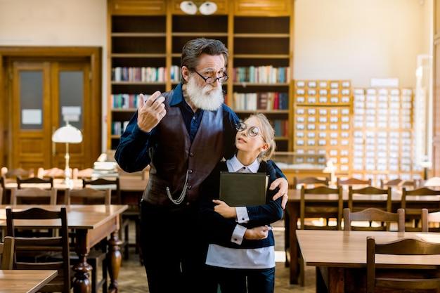 Attraente nonno di 70 anni con gli occhiali che mostra il mondo dei libri nella vecchia biblioteca vintage per sua nipote adolescente sorridente, con in mano un libro e ascoltando suo nonno