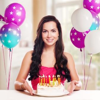 Attraente ragazza adolescente festeggia il suo compleanno con torta