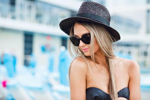 Attraente ragazza bionda con i capelli lunghi seduti in città sull'erba. indossa maglietta, occhiali da sole e cappello neri. sta guardando in basso.