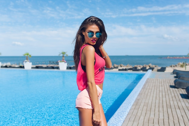 Attraente ragazza bruna con i capelli lunghi è in posa per la fotocamera vicino alla piscina. sta guardando in basso.