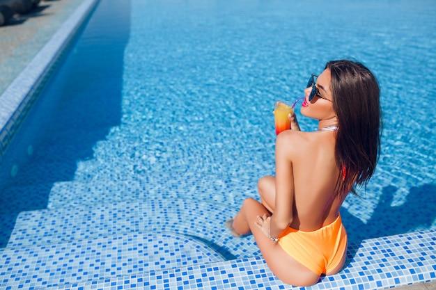 Attraente ragazza bruna con i capelli lunghi è seduta sulle scale per la piscina. ha in mano un cocktail e tiene gli occhi chiusi.