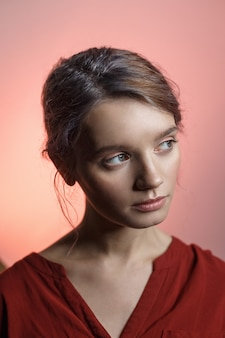 Attraente ragazza caucasica sensuale in camicia rossa guardando lontano e inclinando la testa. ritratto di bellezza su sfondo rosa