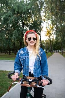 Attraente ragazza che cammina sulla bici nel parco