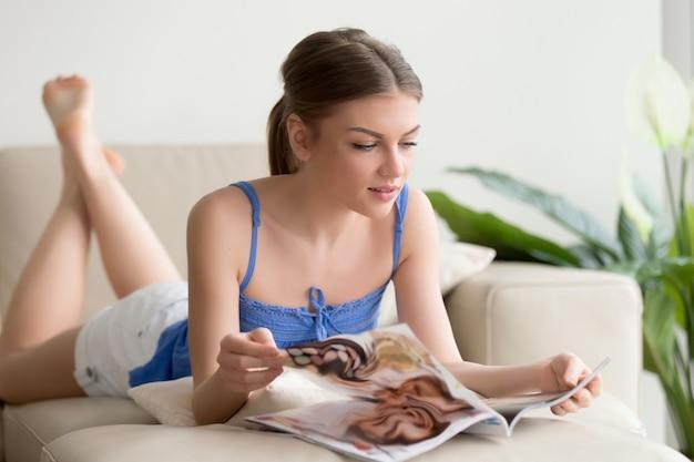 Attraente ragazza che legge la rivista sdraiata sul divano a casa