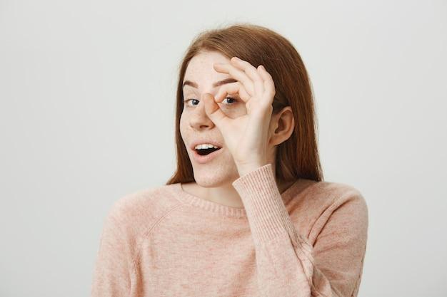 Attraente ragazza rossa carina che mostra il gesto giusto sopra l'occhio, dà l'approvazione