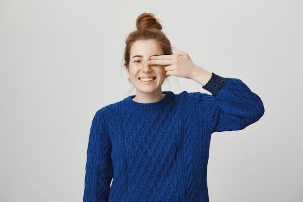 Attraente ragazza rossa spensierata copre un occhio e sorride