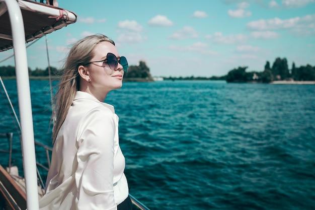Attraente ragazza sorridente in una camicia bianca e occhiali da sole su uno yacht