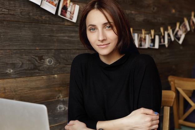Attraente ragazza studentessa bruna che indossa un elegante abito nero tenendo le braccia conserte mentre era seduto davanti al computer portatile, lavorando sul progetto di diploma online, usando la connessione wi-fi gratuita durante la pausa caffè