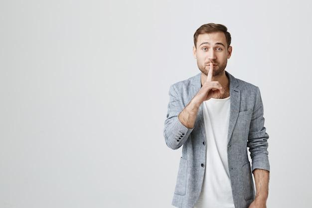 Attraente ragazzo barbuto che chiede di stare zitto, silenzio