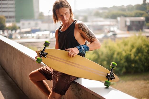 Attraente ragazzo dai capelli lunghi seduto sul parapetto con longboard