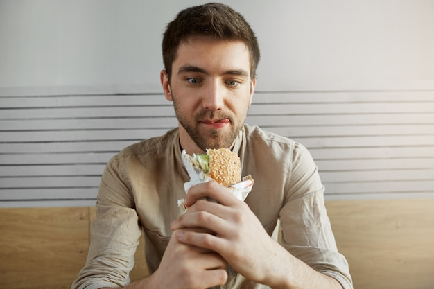 Attraente ragazzo dai capelli scuri seduto nel caffè, guardando con espressione felice a sandwich, essendo felice di mangiare qualcosa dopo tutto il giorno al lavoro. uomo affamato che va a mangiare hamburger.