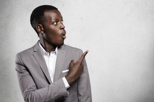 Attraente sbalordito uomo d'affari dalla pelle scura o impiegato in abbigliamento formale che guarda il muro bianco sorpreso, puntando il dito contro lo spazio della copia per il testo o il contenuto pubblicitario