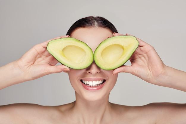 Attraente signora sorridente con perfetta pelle pura e occhiali da avocado